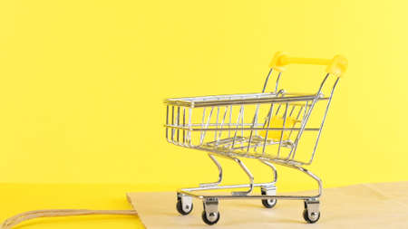empty Shopping cart on a yellow background, closeup. Black Friday Shopping and Discount Concept.