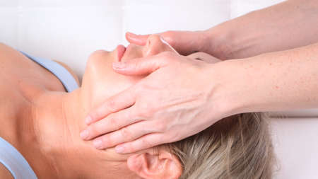 Facial massage beauty treatment. Close up of a young womans face lying on back, getting face lifting massage, pinch and roll technique. Imagens