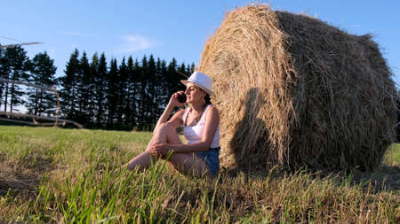 young female talking on a smartphone near a haystack. Rural area. freedom concept.
