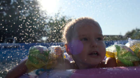 little girl swims in an inflatable ring in the pool in the backyard: Tyumen, Russia - May 12, 2020 Editorial