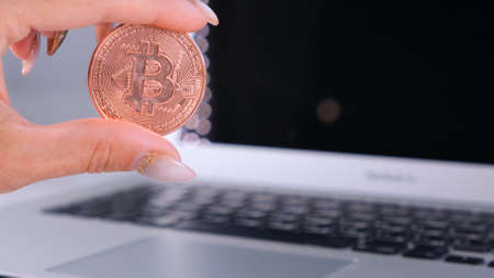 female hand holds golden Bitcoin cryptocurrency coin on laptop, Crypto is Digital Money within the blockchain network, is exchanged using technology and online internet exchange. Financial concept. Imagens