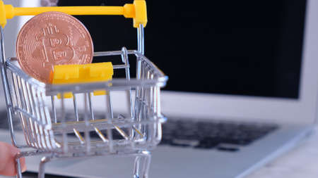Crypto online Shopping concept, shop cart with purchases, Cryptocurrency golden bitcoin coin on laptop background. electronic virtual money Imagens