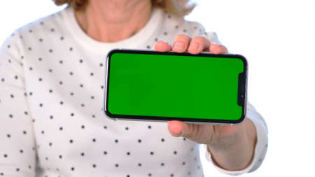 Middle-aged female senora uses an iPhone smartphone with a chroma key screen, copy space, close up. Online shopping concept, use of mobile applications: Moscow, Russia - June 24, 2021. Editorial
