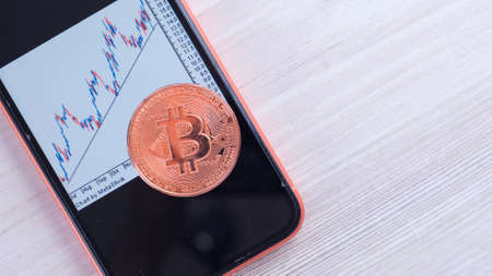 Smartphone with Bitcoin trading chart on the screen. gold Bitcoin Cash coin. Trading on the cryptocurrency exchange: Moscow, Russia - May 31, 2021.