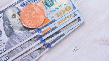 Bitcoin cryptocurrency coins on one hundred US Dollar. Virtual cryptocurrency concept. Bitcoin BTC cryptocurrency coins and banknotes of one US Dollar. BTC vs USD