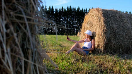 young female makes a selfie on a smartphone near a haystack and talks on video communication. Rural area. freedom concept. Imagens