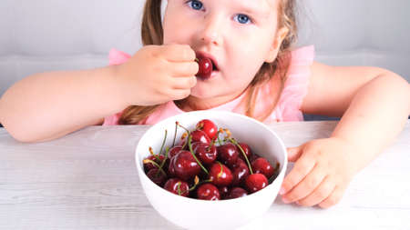 beautiful cute blonde little girl sitting at a light wooden table with a plate of cherries and eating red berries. Healthy eating