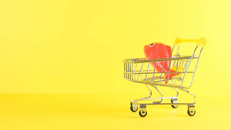 Shopping cart with fish inside on a yellow background, closeup. Black Friday Shopping and Discount Concept Imagens
