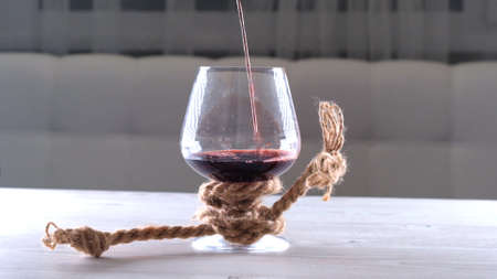 wine is poured into glass is tied with a rope. The concept of alcohol dependence