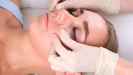 Beautiful woman in salon having facial massage