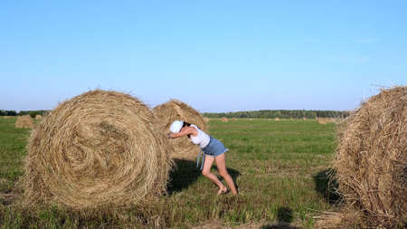 beautiful young girl in a hat pushes a haystack. Rural area. Feminist strong woman concept.
