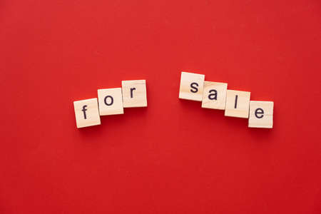 word FOR SALE made of wooden letters on red background with copy space.