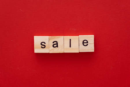word SALE made of wooden letters on red background with copy space.
