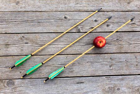bow arrow: flecha manzana perforada. tres flechas en el fondo de madera simbolizan tres intentos de dar en el blanco