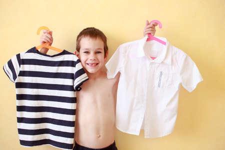 nackter junge: Junge versucht, auf Kleidung. der Junge kauft seine Kleidung: Hemd und T-Shirt