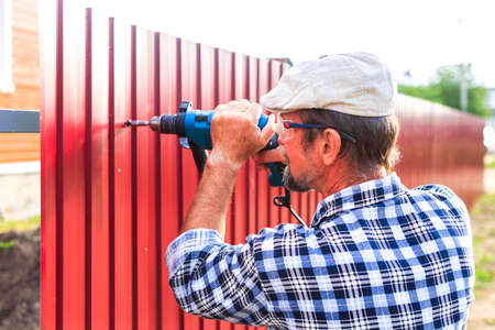 build a metal fence. an elderly man with a drill builds metal fence Foto de archivo