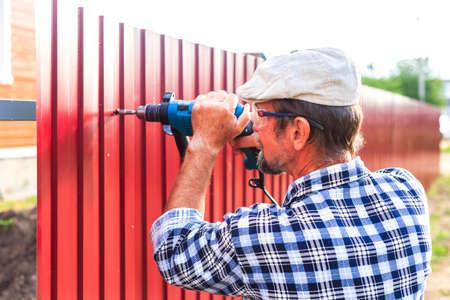 materiales de construccion: construir una valla met�lica. un hombre mayor con un taladro construye cerca del metal