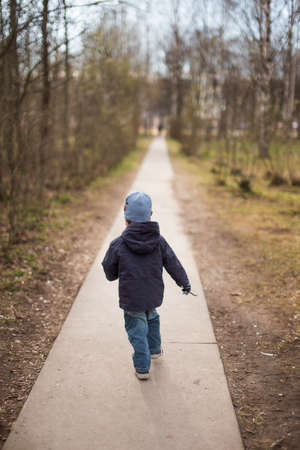 disobedient child: child escape. the child runs on a path in park Stock Photo