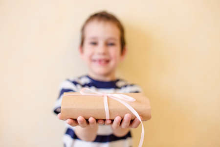 child holds out a gift. the child gives a gift tied with a ribbon