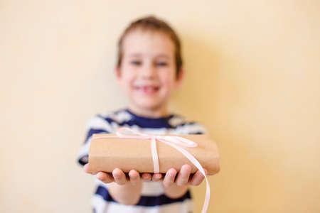dar un regalo: niño sostiene un regalo. el niño da un regalo atado con una cinta
