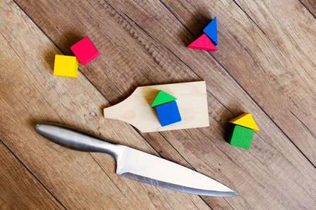 squatter: demolitions. knife and cutting Board with houses out of blocks symbolize the demolition of houses