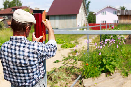 only one senior: man builds a fence. an elderly man makes measurements for the construction of the fence