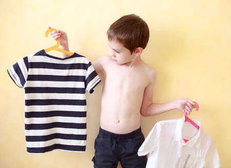 boy  naked: shirt or t-shirt. the boy chooses that to wear a t-shirt or shirt Stock Photo
