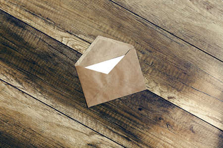 envelope. the envelope of brown paper with a blank white form on wooden background