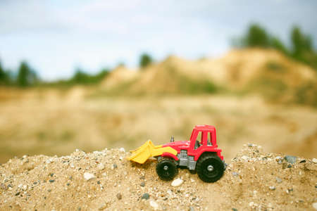 sand quarry: toy excavator. toy excavator at sand quarry Stock Photo