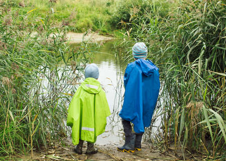 children pond: Children at a pond. two children in raincoats walking in the tall grass by the pond Stock Photo