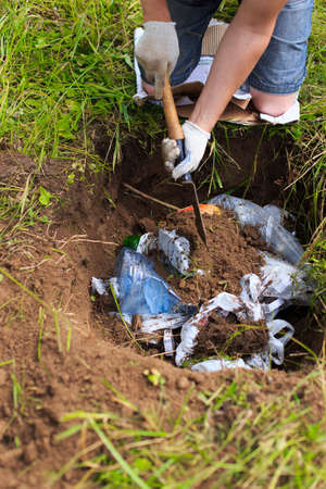 bury: bury trash. man in camping removes household rubbish into a hole Stock Photo