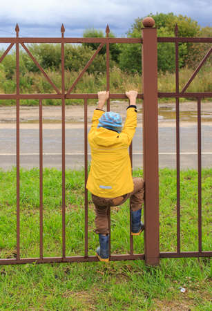 tenacious: way to freedom. Boy going to climb over the high fence