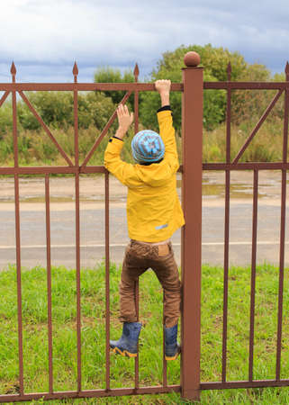 fence: Boy on a fence. the boy climbed onto a high fence Stock Photo