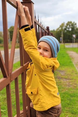 climbing the fence. boy playing on the climbing tall fence Zdjęcie Seryjne