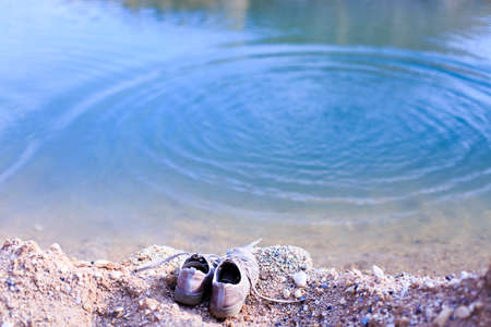 swimming shoes: drowning. shoes on the waterfront and circles on the water symbolize the consequences of unsuccessful swimming Stock Photo