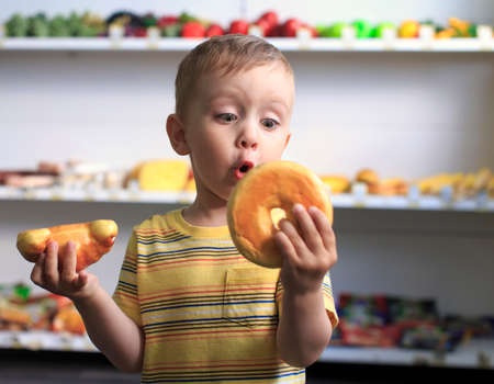 unhealthy eating: donut or croissant. child plays with toy foodlittle child playing with toy plastic sweet food