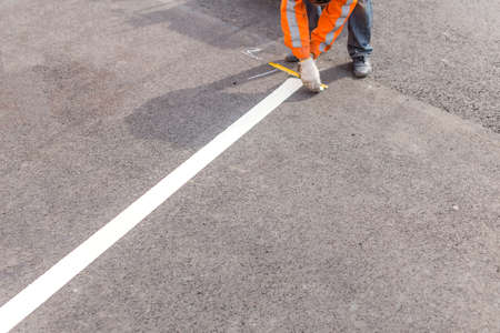 road marking: road line. worker painted on the asphalt road marking Stock Photo