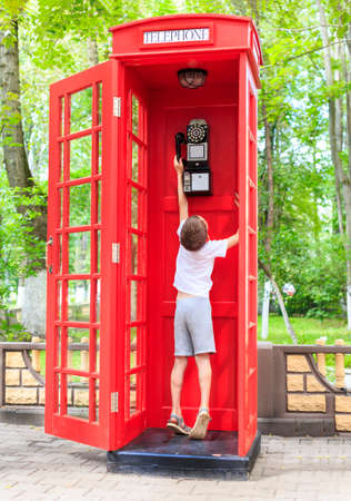 telephone box: boy in a phone booth. the child reaches for the tube in a telephone box in british style Stock Photo