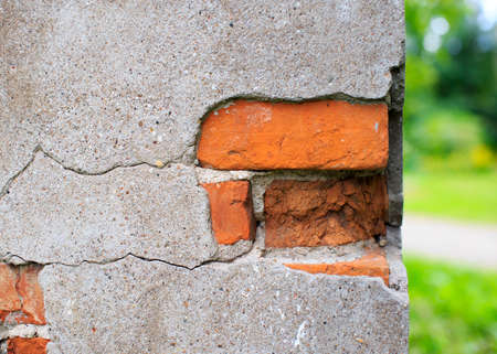 cracked cement: cracks in wall. cracked cement on a brick wall