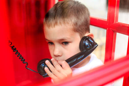 cabina telefonica: llamar a los servicios de emergencia. alarmado por el ni�o habla por tel�fono desde una cabina telef�nica Foto de archivo