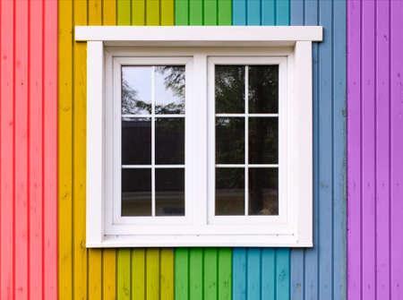 bandera gay: casa de arco iris. pared de madera de una casa pintada en un arco iris de colores Foto de archivo