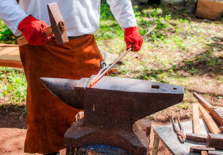 forger: blacksmith at work. blacksmith forges iron bar hitting the hammer on the anvil Stock Photo