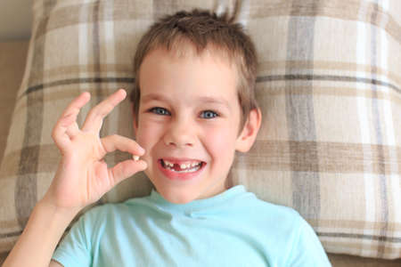 waiting for the tooth fairy. Boy shows gesture OK rejoicing lost baby tooth