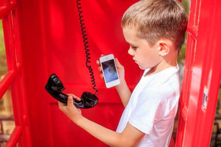 persona de pie: m�vil o fijo. ni�o elige entre m�vil y de l�nea fija en una cabina de tel�fono rojo