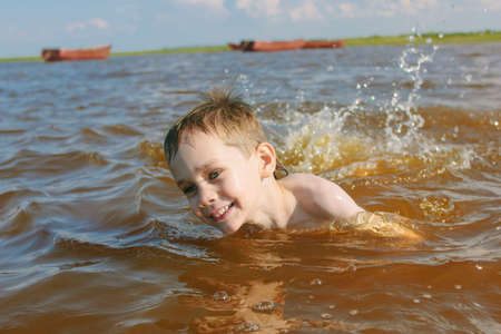 taking the plunge: boy swims. child enjoying a dip in the river