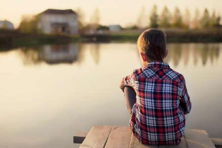 dromen. kind dromen zittend op een houten pier in de buurt van het water en kijken naar het huis en de mensen aan de andere kant Stockfoto
