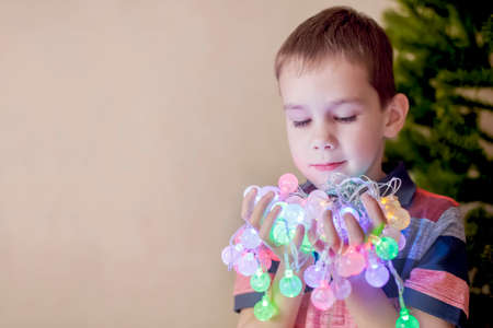 admiration: admiration Christmas lights.Christmas foreboding, anticipation of the holiday. boy decorates Christmas tree and holds in hands Christmas lights