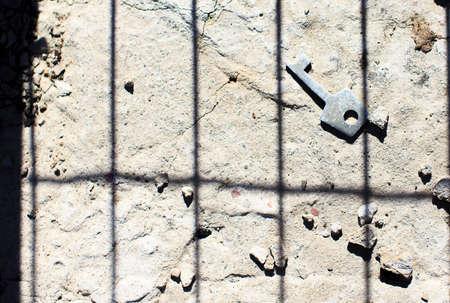 key to freedom: La clave de la Libertad. la sombra de las barras en el piso de concreto y metal clave simboliza el camino hacia la libertad del cautiverio Foto de archivo