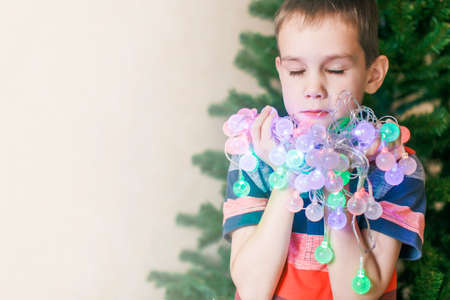 ��beautiful boy�: make a wish under Christmas. beautiful boy covering his eyes with long eyelashes make a wish. He holds in his hands and chest presses to Christmas lights Stock Photo