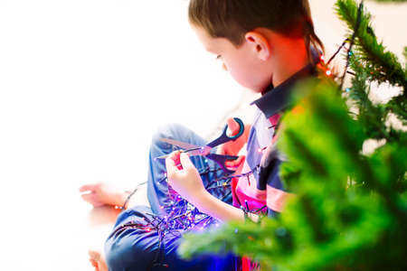 electric shock: one second before the electric shock. curious boy with a pair of scissors in his hand trying dismantle the Christmas lights to see what is inside. over the shoulder view